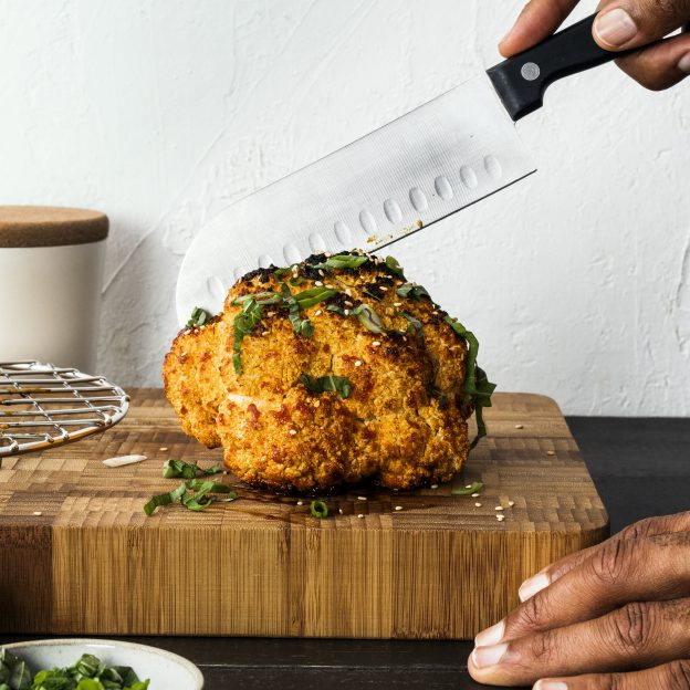Whole Smoked Spicy Cauliflower garnished and being cut Image